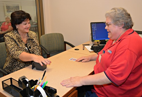 Peninsula Regional Medical Center registrar Terrie Shatney scans the palm of PRMC President/CEO Peggy Naleppa, MS, MBA, Dr.M, FACHE.