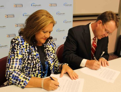 Peninsula Regional CEO/President Peggy Naleppa, left, and Bayhealth CEO/President Terry Murphy sign the agreement creating HealthPartners Delmarva on July 29, 2014.