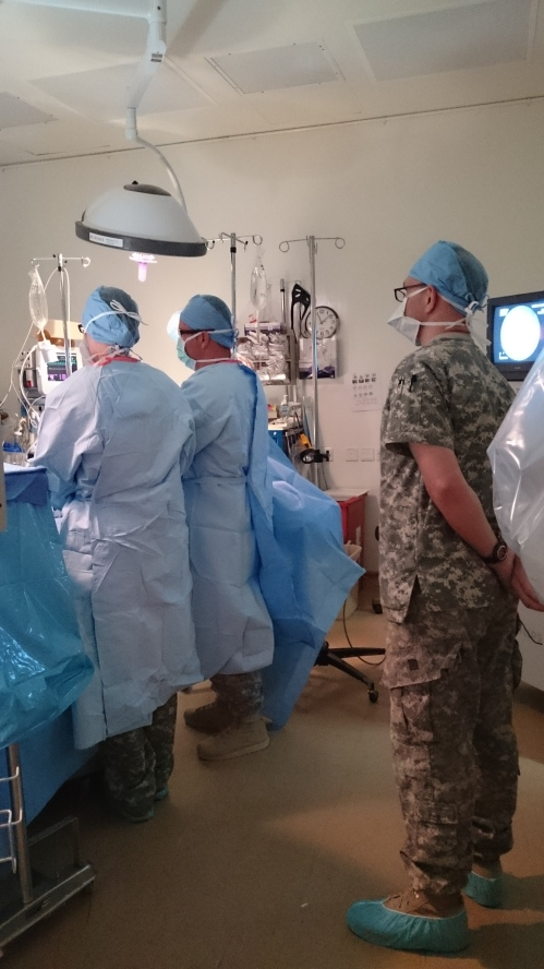 Dr. Daniel McCullough, at the table on the right (wearing the combat boots) performs a laparoscopic appendectomy on a service member.