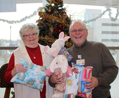 Judy Young donates pillows to PRMC. Accepting the donation is Community Relations Director, Roger Follebout, Jr.
