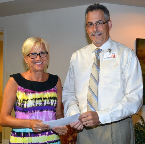 Cindy Hill presents a $5,000 donation from the Ten Mile Miracle to  to Warner Crumb, Executive Director of Orthopedics and Neurosciences, for ALS patients at Peninsula Regional Medical Center.